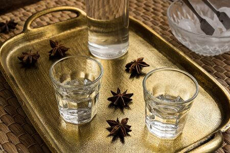 Glasses of traditional drink Ouzo or Raki on bronze dish with anise star seeds Stock Photo