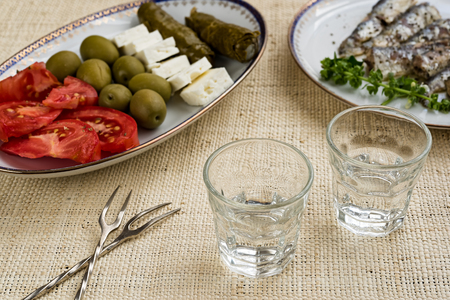 Two glasses of traditional drink Ouzo or Raki and appetizers on natural matting