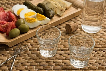 Two glasses and a bottle of traditional drink Ouzo or Raki and appetizers on natural matting Stock Photo
