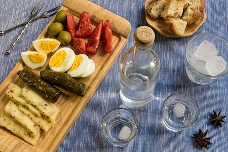 Two glasses and a bottle of traditional drink Ouzo or Raki and appetizers on natural matting Stock Photo - 86412884
