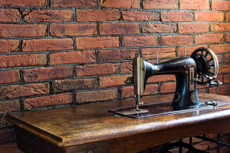 Alte Nähmaschine mit seinem Holztisch nahe einer Wand von roten Backsteinen in Griechenland
