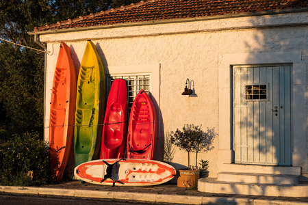 Various colorful canoes for hire, leaned against the wall of a traditional house in Greece Stock Photo