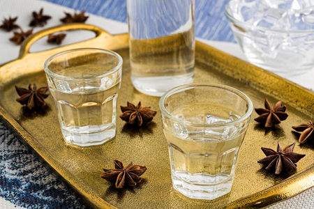 Glasses and bottle of traditional drink Ouzo or Raki on bronze dish with anise star seeds Stock Photo - 105505592