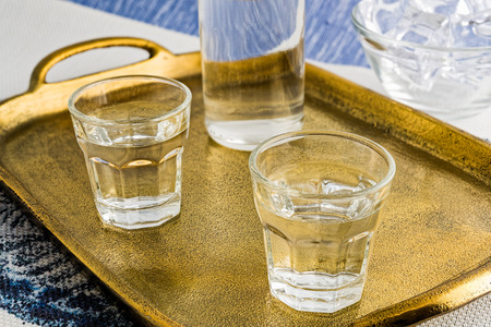 Glasses and bottle of traditional drink Ouzo or Raki on bronze dish Stock Photo
