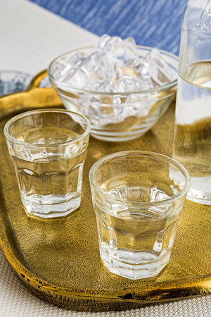 Glasses and bottle of traditional drink Ouzo or Raki on bronze dish Stock Photo - 105505594