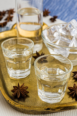 Glasses and bottle of traditional drink Ouzo or Raki on bronze dish with anise star seeds