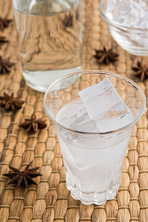 Glass and bottle of traditional drink Ouzo or Raki with anise star seeds on natural matting Stock Photo - 105505597
