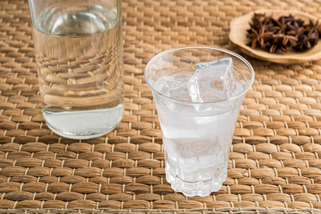 Glass and bottle of traditional drink Ouzo or Raki with anise star seeds on natural matting Stock Photo - 105618413