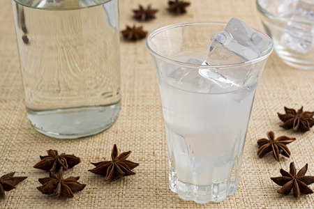Glass and bottle of traditional drink Ouzo or Raki with anise star seeds on natural matting Stock Photo - 105619294