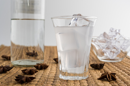 Glass and bottle of traditional drink Ouzo or Raki with anise star seeds on natural matting Stock Photo