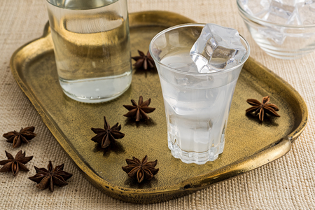 Glass and bottle of traditional drink Ouzo or Raki on bronze dish with anise star seeds