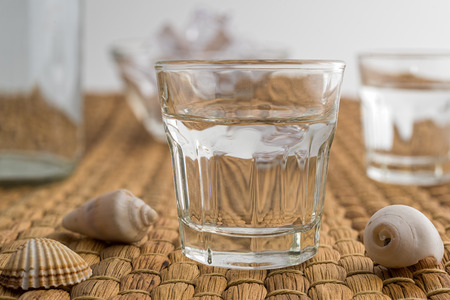 Glasses and bottle of traditional drink Ouzo or Raki with anise star seeds on natural matting