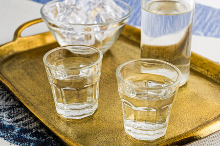 Glass and bottle of traditional drink Ouzo or Raki on bronze dish Stock Photo - 106012567