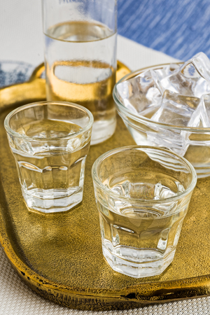 Glass and bottle of traditional drink Ouzo or Raki on bronze dish
