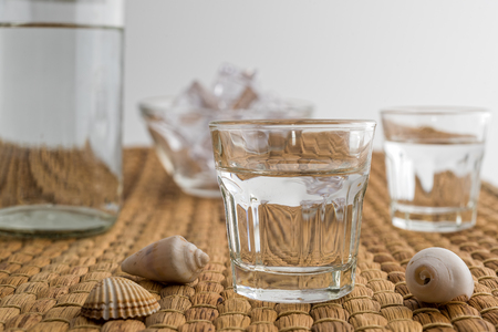 Glasses and bottle of traditional drink Ouzo or Raki on natural matting Stock Photo - 106121060