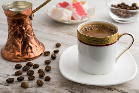 Vintage cup of turkish coffee and traditional bronze coffee pot served on marble with turkish delights Stock fotó