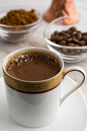 Vintage cup of turkish coffee and traditional bronze coffee pot served on marble