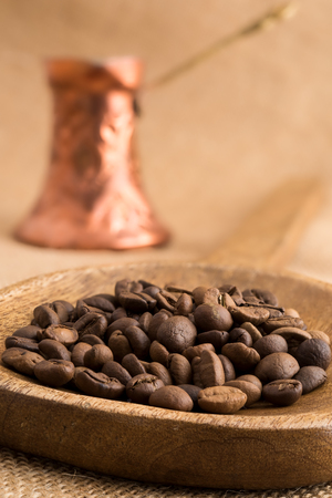 Roasted coffee beans in wooden ladle and traditional bronze coffee pot on sackcloth Archivio Fotografico