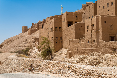 A man rides his donkey in front of buildings made from mud and stone on May 8, 2007 in Al Hajarayn, Yemen. Among other arabic countries, in 2012 Yemen became a site of civil conflicts, which still continue.