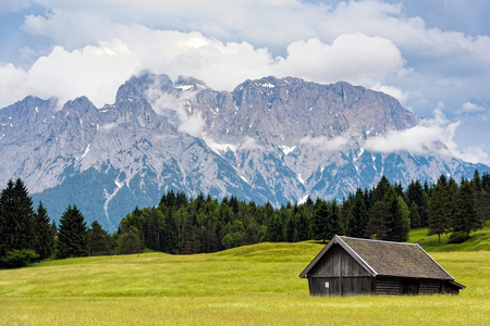 Wooden hut near Zugspitze, the highest mountain of Germany at the Bavarian Alps Stock Photo