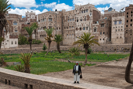 A man in traditional clothes stands in front of multi-storey buildings made of stone on May 4, 2007 in Sanaa, Yemen. The Old City of Sanaa is a UNESCO World Heritage City.