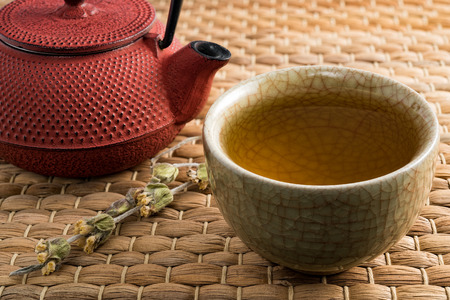 Cup of tea and japanese traditional style red teapot with dry tea on natural matting