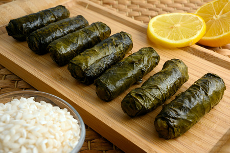Delicious stuffed grape leaves (the traditional dolma of the mediterranean cuisine) on wooden tray board with lemon and small glass bowl of raw rice