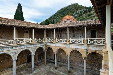 Part of the byzantine archaeological site of Mystras in Peloponnese, Greece. View of the interior courtyard of the Archaeological Museum of Mystras and the Castle of Villeharduin on the top of the hill