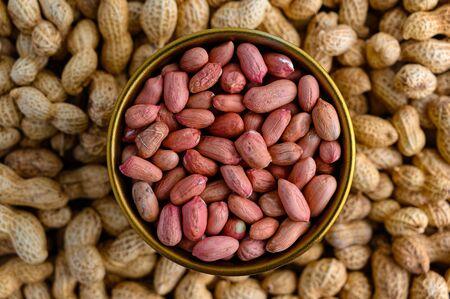 Bronze bowl of peeled peanuts and peanuts in nutshell Stockfoto