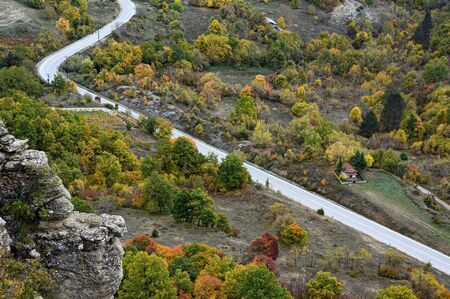 Landscape with autumn colorful foliage and winding road on Mount Grammos in northwestern Greece