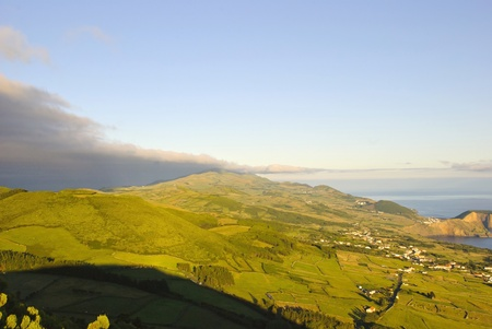 agriculture azores: Green meadows of Sao Jorge island with Pico mountain behind, Azores, Portugal Stock Photo