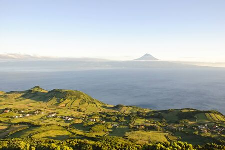 Green meadows of Sao Jorge island with Pico mountain behind, Azores, Portugal photo