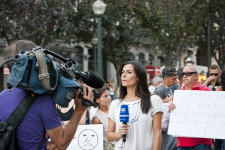 PORTO, PORTUGAL - SEPTEMBER 15: Journalist making reportage for portuguese national television (RTP) with protestors against government spending cuts and tax rises in Aliados square, Porto on September 15, 2012. Editorial