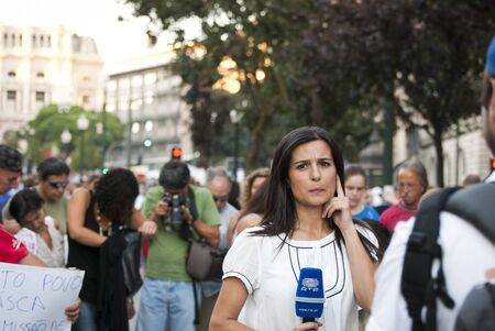 PORTO, PORTUGAL - SEPTEMBER 15: Journalist making reportage for portuguese national television (RTP) with protestors against government spending cuts and tax rises in Aliados square, Porto on September 15, 2012.