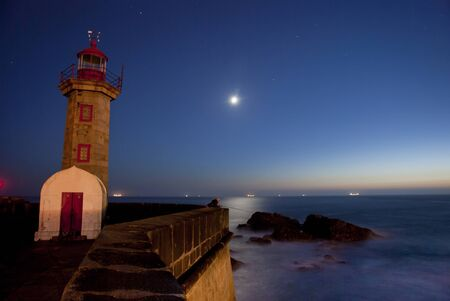 Lighthouse at night with ocean, moon, rocks and stars on the sky photo