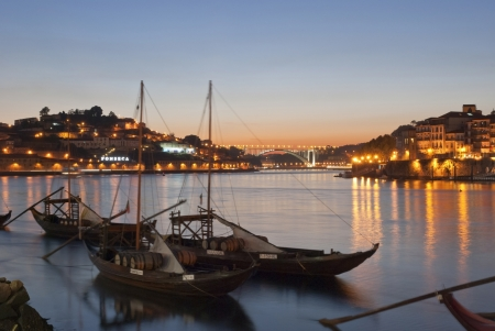 PORTO, PORTUGAL - SEPTEMBER 2, 2012: Traditional boats with wine casks at Douro river in Porto, Portugal in september 2012. Those boats were used for transporting the porto wine from Douro valley.