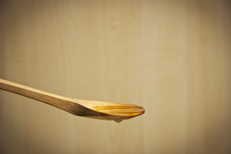 Olive oil running over the wooden spoon, on retro background photo