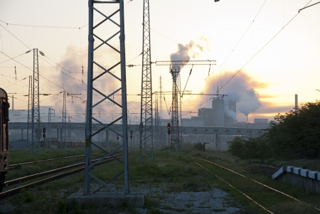 Heavy industry complex chimneys behind the railway in sunrise photo