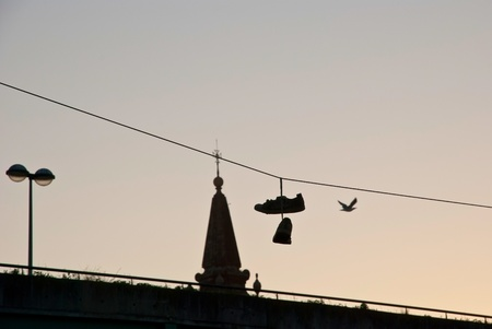 cable tangle: Silhouette of shoes hanging on the cable over the city
