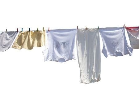 Laundry drying on the rope outside on a sunny day, isolated on white photo