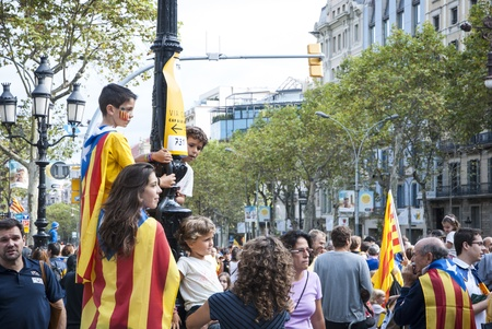 separatism: BARCELONA, SPAIN - SEPTEMBER 11: Kids waving with flags during Catalan Way, silent demonstration for independent Catalonia in Barcelona, Spain on September 11, 2013