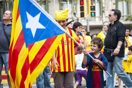 BARCELONA, SPAIN - SEPTEMBER 11: Kids waving with flags during 'Catalan Way', silent demonstration for independent Catalonia in Barcelona, Spain on September 11, 2013