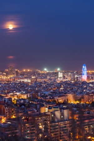 Barcelona at night with full moon and torre agbar, Catalunya, Spain photo