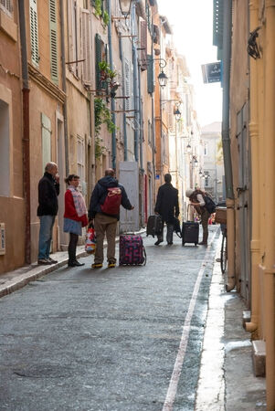 MARSEILLE, FRANCE - OCTOBER 31  People arriving to hotel in narrow street of Marseille old town  Taken in Marseille, France on October 31, 2013