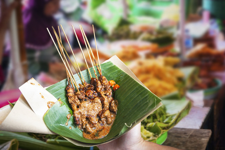 Indonesian chicken satay served in leaf on the food market