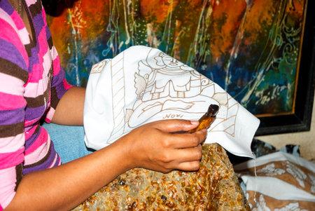 indonesian woman: Yogyakarta, Indonesia - septiembre, 13: Mujer de Indonesia aplicando vax en batik en el taller. Batik es arte tradicional hecha aplicando vax y tinte en la tela. Tomado en Yogyakarta, Indonesia el 13 de septiembre 2014