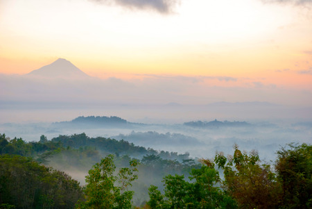 Colorful sunrise over jungle with Merapi volcano behind and Borobudur temple, Indoneisa photo