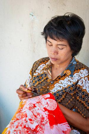 indonesian woman: Yogyakarta, Indonesia - septiembre, 15: Mujer de Indonesia aplicando vax en batik en el taller. Batik es arte tradicional hecha aplicando vax y tinte en la tela. Tomada En Yogyakarta el 15 de septiembre 2014