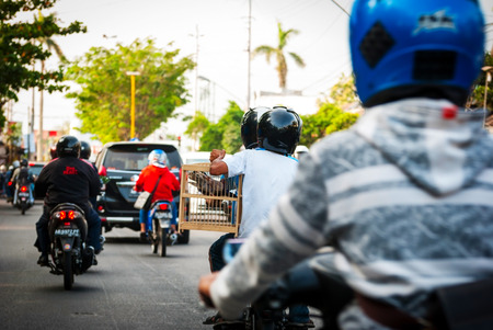 YOGYAKARTA, INDONESIA - SEPTEMBER 15: Driving in a local road between motorbikes and cars in Yogyakarta, Indonesia on Sept. 15, 2014.