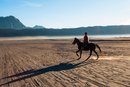 Horse rider at volcanic plateau of Mount Bromo, Java, Indonesia photo